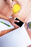 Накладные расходы женственных рук держа smartphone и стекло апельсинового сока Стоковые Фото