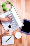 Накладные расходы женственных рук используя компьтер-книжку и кофе держать Стоковые Фото