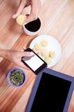 Накладные расходы женственных рук используя smartphone и печенье Стоковое Фото