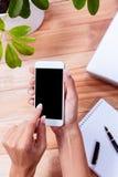 Накладные расходы женственных рук используя smartphone Стоковые Изображения