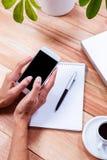 Накладные расходы женственных рук используя smartphone Стоковое Фото