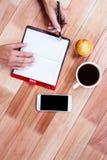 Накладные расходы женственных рук писать на повестке дня Стоковая Фотография
