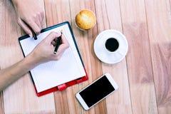 Накладные расходы женственных рук писать на повестке дня Стоковые Изображения