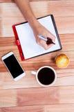 Накладные расходы женственных рук писать на повестке дня Стоковые Изображения RF