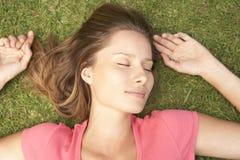 Накладные расходы женщины лежа на траве Стоковые Изображения