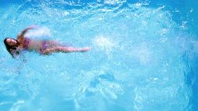 Накладные расходы заплывания брюнет в бассейне на солнечный день сток-видео