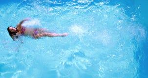 Накладные расходы заплывания брюнет в бассейне на солнечный день видеоматериал