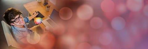 Накладные расходы новаторское тысячелетнего на компьютере с таблеткой графиков и красным переходом bokeh Стоковое Изображение