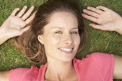 Накладные расходы усмехаясь женщины лежа на траве Стоковые Фото