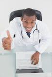 Накладные расходы усмехаясь мужского доктора с компьтер-книжкой показывать большие пальцы руки вверх Стоковое Изображение
