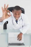 Накладные расходы усмехаясь доктора с компьтер-книжкой показывать одобренный знак Стоковые Фото