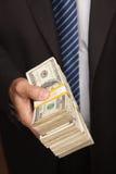 наличные деньги бизнесмена вручая над стогом стоковые фото