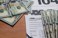 Налоговая форма 1040, доллары на деревянном столе стоковая фотография