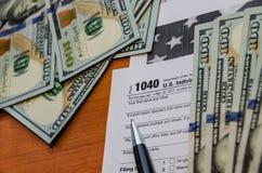 Налоговая форма 1040 и доллары стоковые изображения