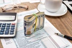 налоговая форма, компьтер-книжка, кофе и доллар Стоковые Изображения