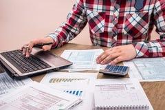 Налоговая форма человека заполняя с бизнес-отчетом, Стоковая Фотография
