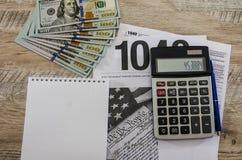Налоговые формы 1040, калькулятор, доллары, блокнот и ручка на деревянной предпосылке стоковое фото