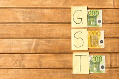 Налог товары и услуги Надпись GST с банкнотами на woode стоковая фотография rf