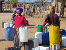 НАМИБИЯ, Kavango, 15-ое октября: Женщины в воде деревни ждать Kavango было зоной с самым высоким левом бедности Стоковая Фотография RF