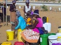 НАМИБИЯ, Kavango, 15-ое октября: Женщины в воде деревни ждать Kavango было зоной с самым высоким левом бедности Стоковое Изображение RF