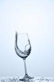 Намочите брызгать от опрокинутой рюмки с более чистой водой пока стоящ на стекле против светлой предпосылки стоковое фото rf