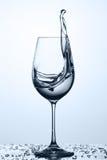 Намочите брызгать от рюмки с выпивая более чистой водой пока стоящ на стекле против светлой предпосылки стоковые изображения rf