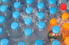 Намочите в бутылках прозрачной пластмассы выдержанных в холодной воде с I Стоковые Фото