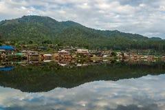 Намочите деревню на крае реки перед горой в сельской местности Стоковая Фотография