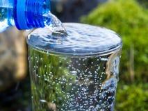 Намочите лить в стекло от бутылки стоковое изображение