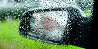 Намочите падения или падения дождя на стекле автомобиля запачканная предпосылка фланк Зеркало автомобиля стоковая фотография