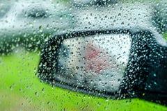 Намочите падения или падения дождя на стекле автомобиля запачканная предпосылка фланк Зеркало автомобиля стоковая фотография rf