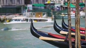 Намочите туристов нося в Венеции, гондол такси припаркованных вдоль канала, sightseeing акции видеоматериалы
