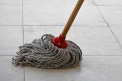 Намочите mop на пакостной плитке Стоковые Изображения