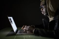 Нападение хакера сервер в темноте Сервер мотыги хакера Афро американский от компьтер-книжки в темноте стоковое фото rf
