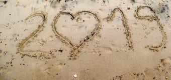 2019 написанное на песке моря с сердцем сформировало 0 Стоковое фото RF