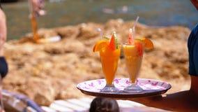 Напитки официанта служа на пляже, Египте Официант держа поднос с тропическими соками акции видеоматериалы