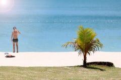 Напитки питья мальчика на пляже во время лета Стоковое фото RF