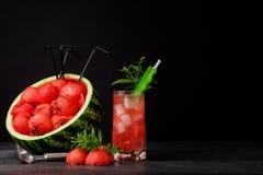 Напиток арбуза с кубами и мятой льда на черной предпосылке Сочная и зрелая большая ягода с черными семенами скопируйте космос Стоковое фото RF