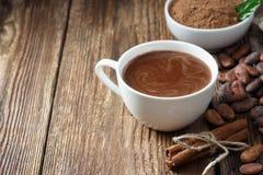 Напиток какао в белых кружке, буром порохе и бобах кака стоковое фото