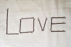 Напишите влюбленность написанную hairpins-ignoramuses на бежевой предпосылке Стоковое Изображение RF