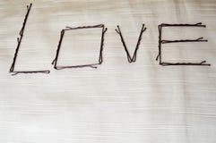 Напишите влюбленность написанную hairpins-ignoramuses на бежевой предпосылке Стоковое фото RF