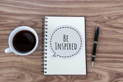 Напоминание собственной личности Вдохновляющие мотивационные закавычат быть воодушевленным с текстом на блокноте, ручке и чашке ч стоковые изображения