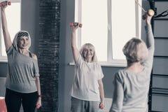 Напористые женщины повторяя разминку гантелей после их тренера стоковая фотография rf