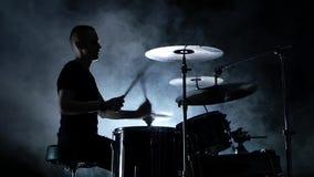 Напористый музыкант играет хорошую музыку на барабанчиках Черная закоптелая предпосылка Взгляд со стороны силуэт движение медленн сток-видео