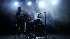 Напористый музыкант играет хорошую музыку на барабанчиках Черная закоптелая предпосылка силуэт сток-видео