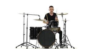 Напористый профессиональный музыкант играет хорошую музыку на барабанчиках Белая предпосылка движение медленное акции видеоматериалы