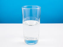 Наполовину опорожните или наполовину полное стекло воды на белой таблице (Для думать позитва) Стоковая Фотография