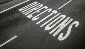` Направления ` дорожного знака на земле асфальта Стоковая Фотография RF