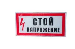Напряжение тока стойки знака вися на проводах стоковое фото