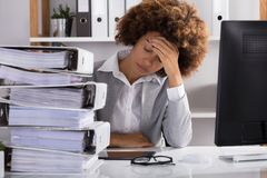 Напряжённая коммерсантка сидя в офисе стоковые фотографии rf